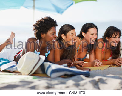Women relaxing on beach blanket together - Stock Photo