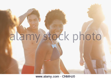 Friends in swimsuits walking on beach - Stock Photo