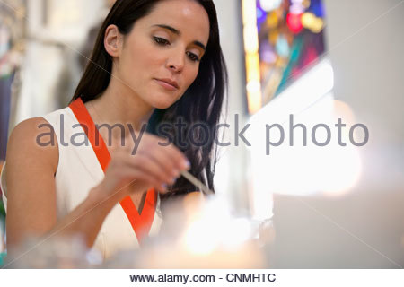 Woman lighting candles in church - Stock Photo