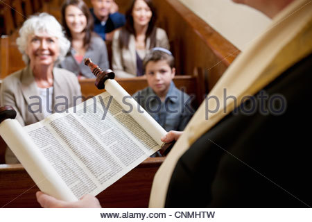 Rabbi reading from Torah scrolls in synagogue - Stock Photo