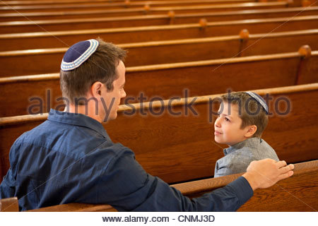 Father and son wearing yarmulkes in synagogue - Stock Photo