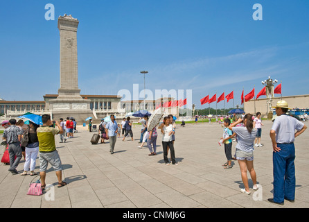 Chinese tourists in Tiananmen Square taking photographs of each other with The Monument to the People's Heroes and - Stock Photo