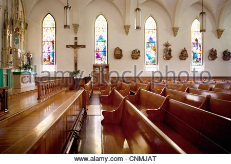 Pews and stained glass windows in church - Stock Photo