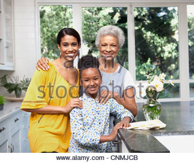Older woman with daughter and granddaughter in kitchen - Stock Photo