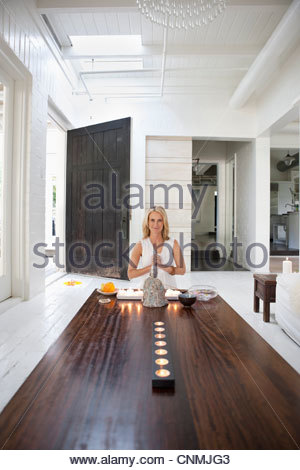 Woman meditating with candles and Buddha statue - Stock Photo
