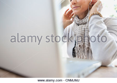 Older woman listening to headphones in laptop - Stock Photo