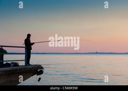 Lone fisherman at dusk on Lake Garda, Italy - Stock Photo