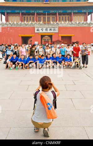 Tourists taking photographs of each other outside the Gate of Divine Prowess (main exit) of the Forbidden City. - Stock Photo