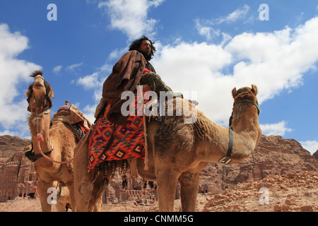 A Bedouin in front of the Royal tombs in Petra trying to hire tourists for a ride with his camels, Jordan. - Stock Photo