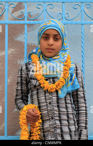 A Jordanian girl with floral wreaths welcoming visitors at the entrance of a spa and holiday resort. Himmeh, Jordan. - Stock Photo