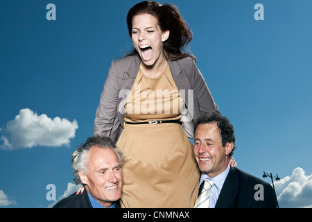 Businesswoman climbing on colleagues - Stock Photo