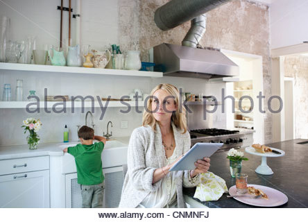 Mother using tablet computer in kitchen - Stock Photo