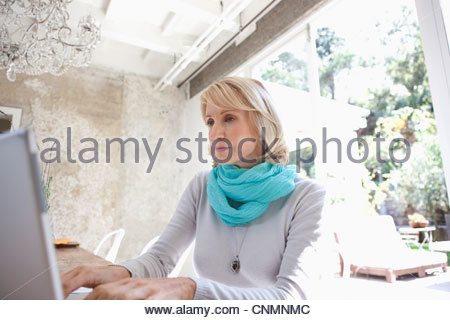 Woman using laptop at dining room table - Stock Photo