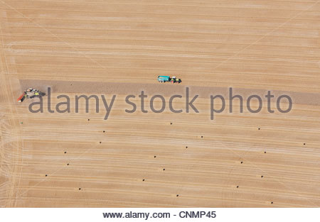 Aerial view of tractors at work in crop fields - Stock Photo