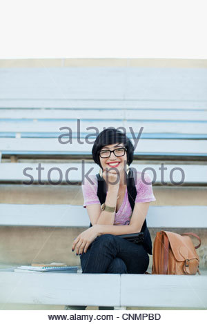 Smiling student sitting on bleachers - Stock Photo