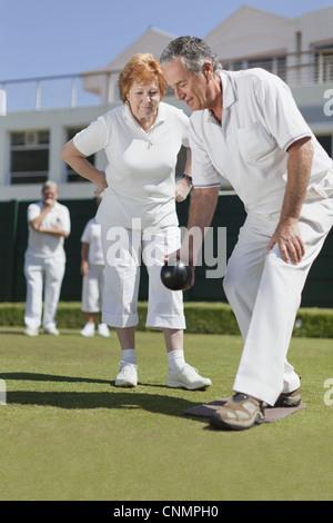 Man teaching woman lawn bowling - Stock Photo
