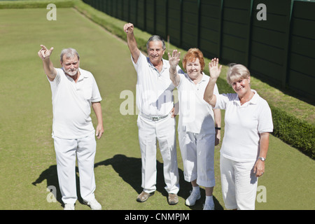 Older people waving from lawn - Stock Photo