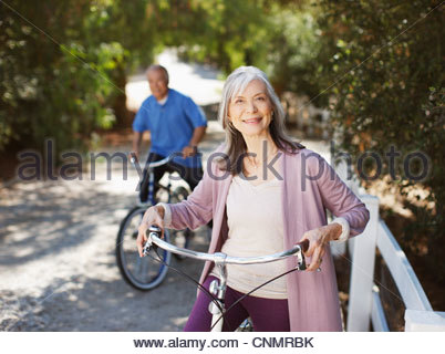 Smiling older couple riding bicycles - Stock Photo