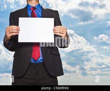 Businessman holding blank card - Stock Photo
