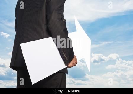 Businessman holding blank arrow - Stock Photo