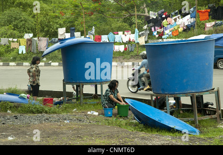 Refugees recent volcanic eruption washing clothes beside big vats water Maguwo Mount Merapi Central Java Indonesia - Stock Photo