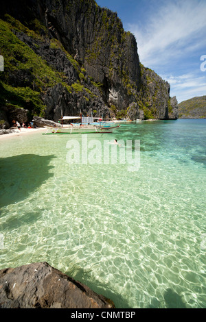 Outrigger boats on a small bay off the steep limestone coast of Tapiutan Island, Bacuit archipelago, El Nido, Palawan, - Stock Photo