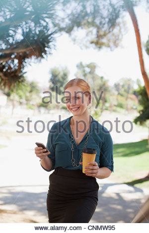 Businesswoman using cell phone in park - Stock Photo