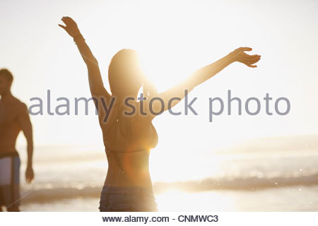 Woman in bikini cheering on beach - Stock Photo