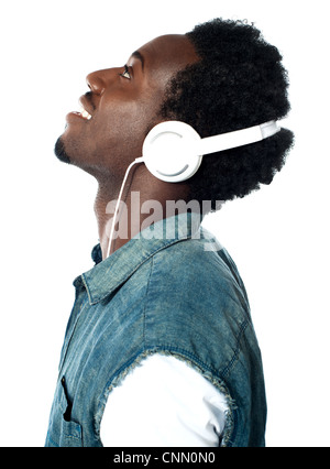 A handsome young boy listening to music on his mp3 player, looking up - Stock Photo