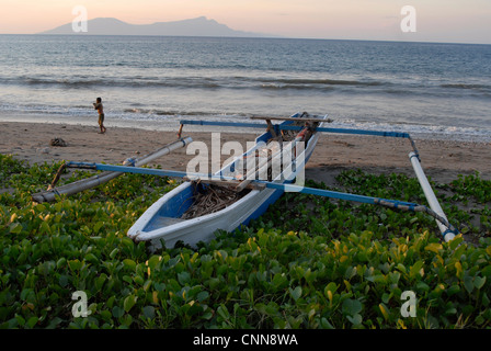 A traditional outrigger fishing boat on the beach in Dili Timor Leste with the island of Atauro on the horizon - Stock Photo