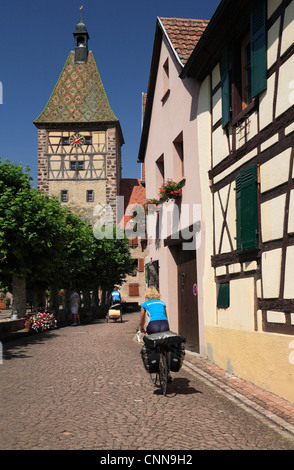 Touring cyclists riding towards half timbered clock tower in the town wall in  Bergheim Alsace France - Stock Photo