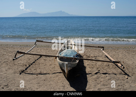 Traditional  fisherman's outrigger on the beach in Dili Timor Leste, with Atauro island on the horizon. - Stock Photo