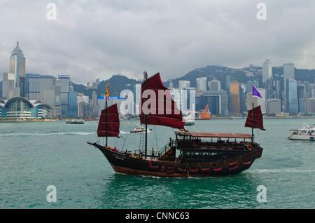 Junk style tourist boat sailing in Victoria Harbor, Hong Kong skyline, China - Stock Photo