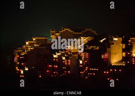 Night view of traditional houses along Wuyang River with reflection in the water, Zhenyuan, Guizhou, China - Stock Photo