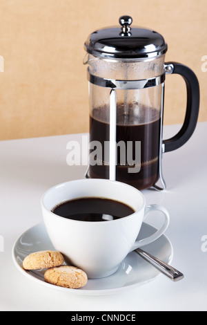 Photo of a cup of coffee with Amaretti biscuits on the saucer and a cafetiere full of freshly brewed coffee.