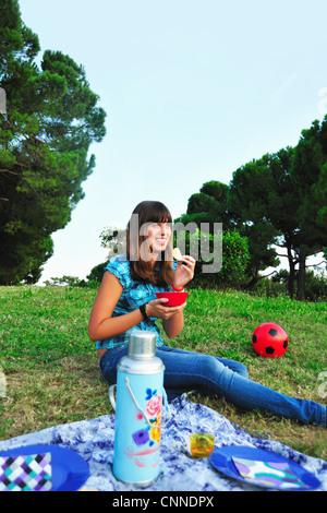 Teenage girl eating at picnic - Stock Photo