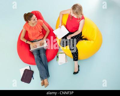 Businesswomen working in bean bag chairs - Stock Photo
