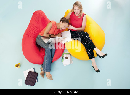 Businesswomen laughing in bean bags - Stock Photo
