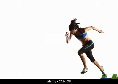 Athlete taking off from starting block - Stock Photo
