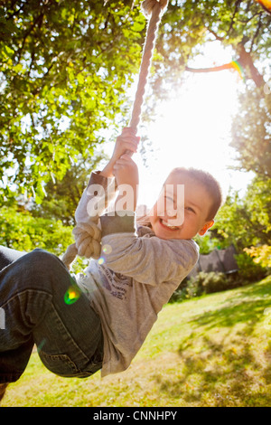 Boy playing on rope swing in backyard - Stock Photo