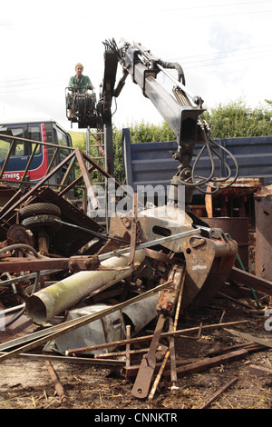 Metal recycler collecting assorted scrap metal with mechanical grabber on farm, Powys, Wales, july - Stock Photo