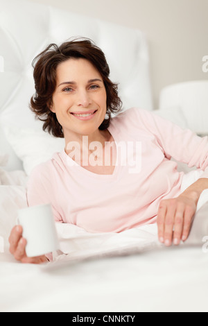 Smiling woman reading newspaper in bed - Stock Photo