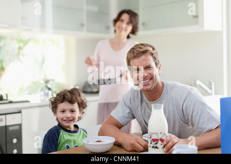 Family eating breakfast in kitchen - Stock Photo