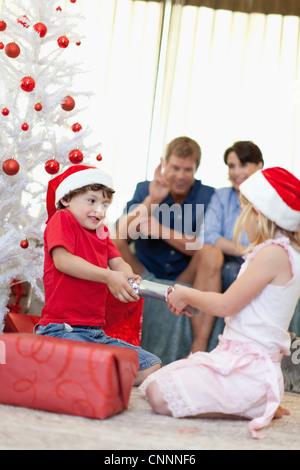 Children opening Christmas cracker - Stock Photo