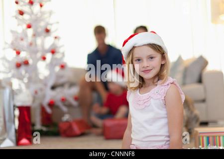 Smiling girl wearing Santa Claus hat - Stock Photo