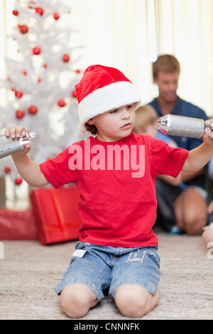 Boy opening Christmas cracker by himself - Stock Photo