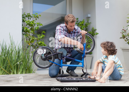 Father helping son fix bicycle - Stock Photo