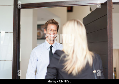 Business people smiling at each other - Stock Photo