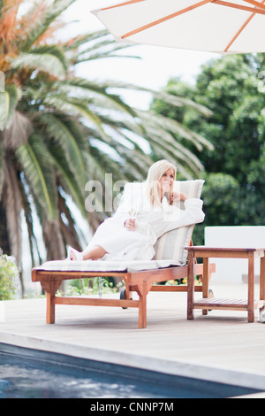 Woman in bathrobe relaxing by pool - Stock Photo