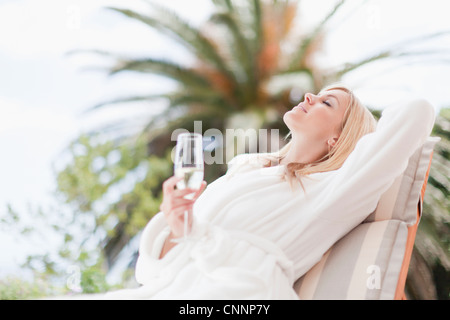 Woman in bathrobe relaxing in lawn chair - Stock Photo